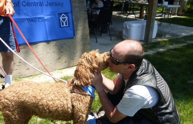 Man getting kissed by dog at Caregiver Event